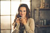 stock photo of comfort  - Head and shoulder shot of a brunette woman in comfortable clothing is smiling gently over the top of her coffee cup - JPG