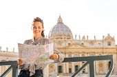 stock photo of balustrade  - Leaning against a balustrade a smiling woman tourist is holding and reading a map of Vatican City - JPG
