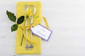 image of yellow buds  - Yellow and white theme wedding table place setting with antique silverware napkin and yellow rose bud on white shabby chic table - JPG