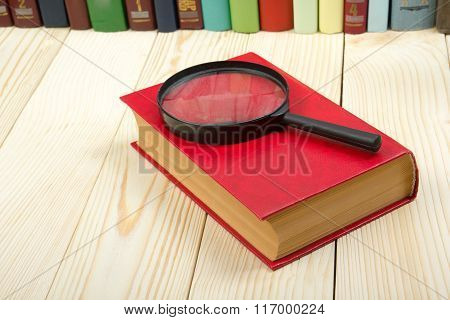 Composition with hardback book and magnifying glass on the table. Back to school, copy space. Educat