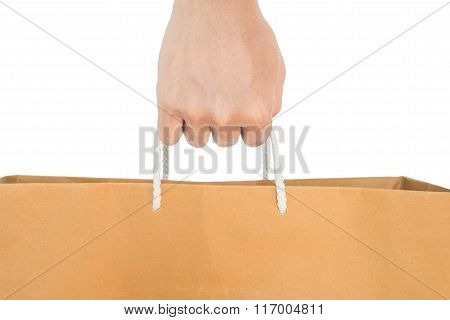 Hand holding reuse paper bag, isolated on white background