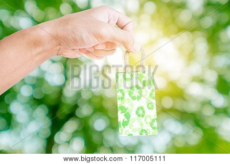 Hand holding green little recycle bag, with green bokeh background