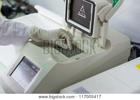 Gloved hand entering sample in lab device
