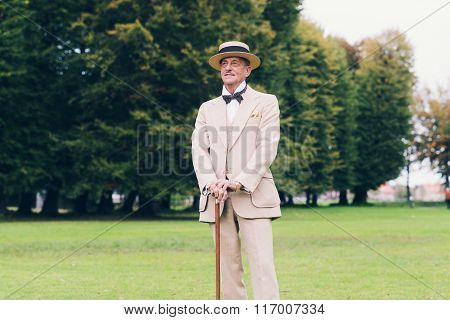 Wealthy Dandy Standing With Cane In Garden.