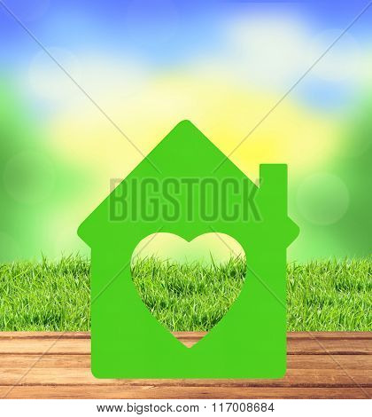 Home Icon On Wooden Table, Blurred Nature Background And Green Grass
