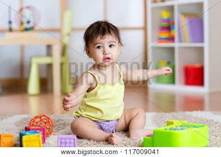Child girl sitting among toys on carpet at home
