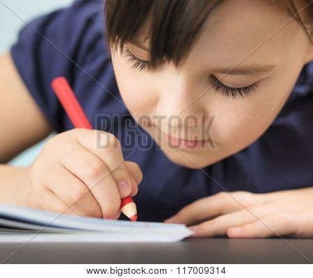 Cute cheerful child drawing using pencil while sitting at table, extreme closeup