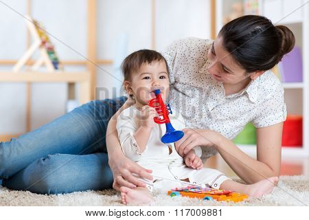 baby and her mother play musical toys