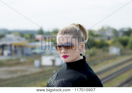 Portrait Of The Beautiful Woman Against Railway Tracks
