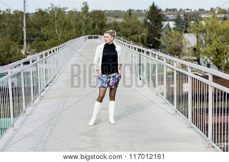 The Sexy Woman In A White Jacket And White Boots On The Bridge