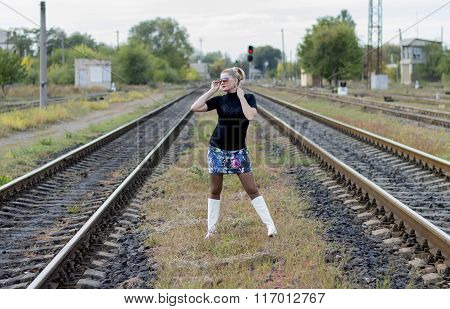 The Beautiful Woman In Sunglasses Between Two Railway Tracks