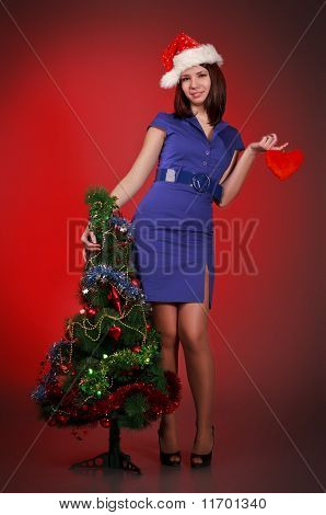 Girl With Toy Heart Near Christmas Tree