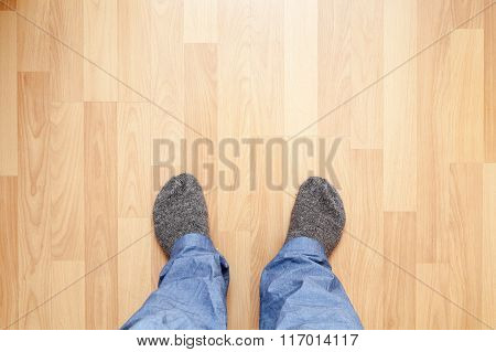 Male Feet In Blue Pants And Gray Woolen Socks