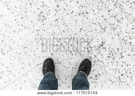 Male Feet Standing On Snowy Winter Road