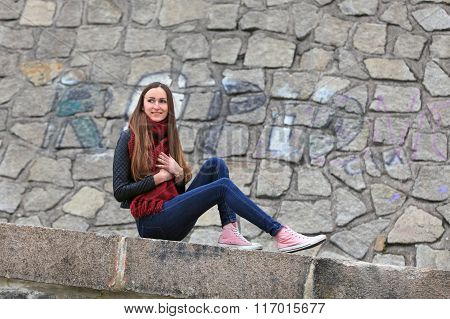 Beautiful girl wearing leather jacket, blue jeans and pink sneakers