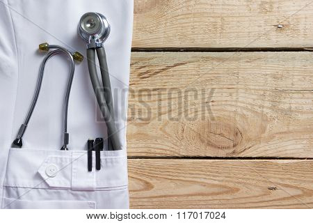 Doctor lab white coat pocket with pen, stethoscope, close-up shot on vintage wooden background. Copy