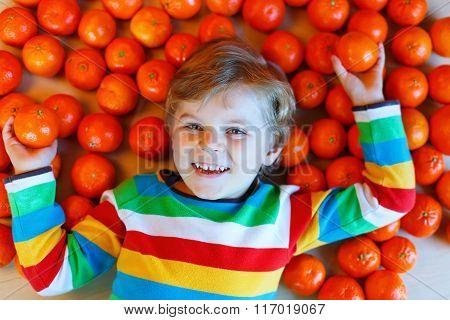 Little kid boy with healthy mandarin oranges fruits