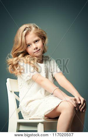 Fashion shot of a pretty little girl with beautiful blonde hair wearing white dress. Studio shot. Kid's beauty, fashion.