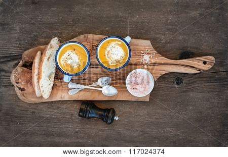Homemade pumpkin cream soup in enamel mugs with herbs and fresh bread slices on olive serving board