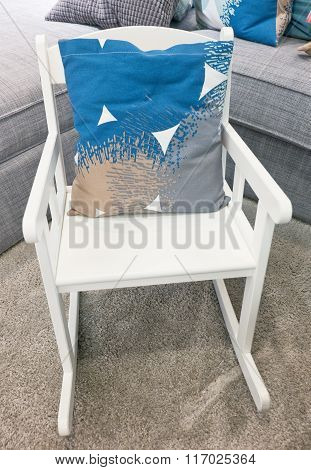 Bright Pillow On A White Rocking Chair
