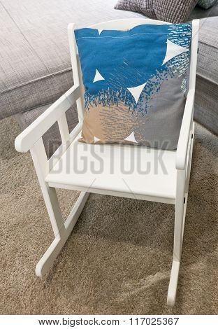 Decorative Pillow On A White Rocking Chair