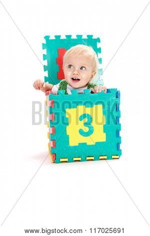 little child baby playing with numbers puzzles smiling isolated on white on white background studio shot learning counting 1 year sitting in the box