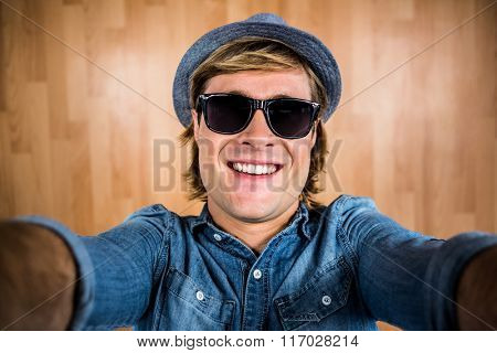 Crazy hipster wearing sunglasses against wooden wall