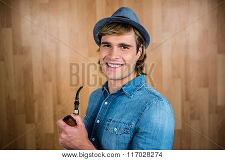 Cheerful hipster holding pipe against wooden wall
