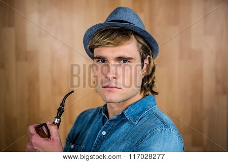 Serious hipster holding pipe against wooden wall
