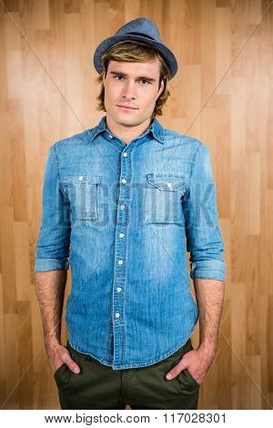 Serious hipster putting his hands in pockets against wooden wall
