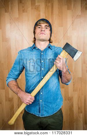 Front view of hipster standing with axe against wooden wall