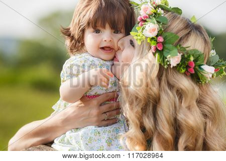 Happy mother with little daughter on the green meadow
