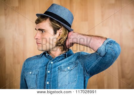 Serious hipster putting hand behind head against wooden wall