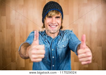 Smiling hipster with thumbs up looking at camera