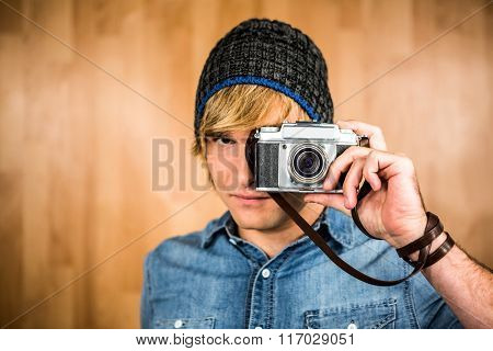 Serious hipster man taking picture with digital camera