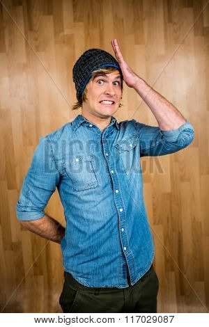 Surprised hipster man staring at camera with wooden background