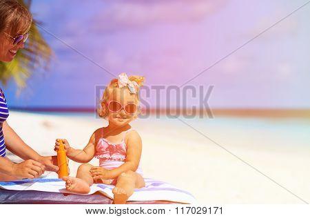 cute little girl with sunblock cream on beach