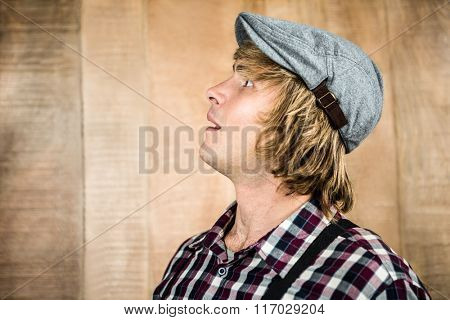 Side view of surprised blond hipster smiling at camera