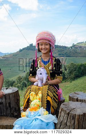 Unidentified tribe girls in traditional dress poses for the camera at Mon jam in Chiang Mai