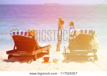 family with kid playing on tropical beach