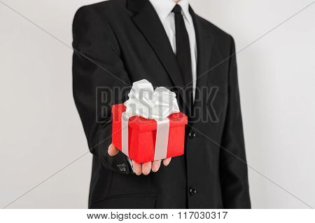 Theme Holidays And Gifts: A Man In A Black Suit Holds Exclusive Gift Wrapped In Red Box With White R
