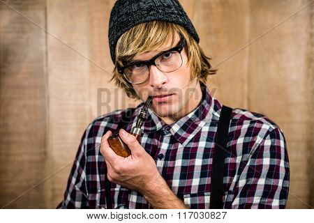 Serious blond hipster smoking a pipe staring at camera