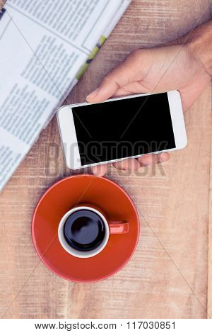 Overhead view of person using smart phone by coffee and document on table