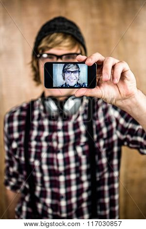 Smiling blond hipster taking selfie with wooden background