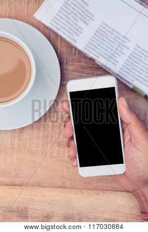 Overhead view of hand holding smart phone by coffee and newspaper on table