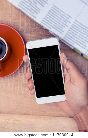 Overhead view of person using smart phone by coffee and newspaper on table