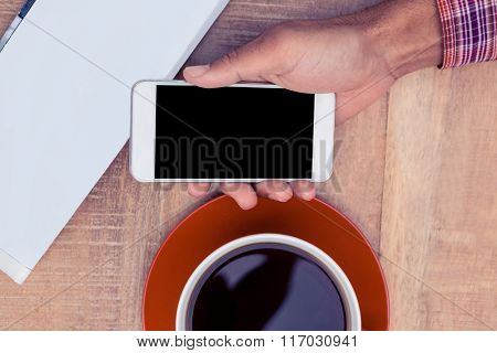 Overhead view of person using smart phone on desk by coffee