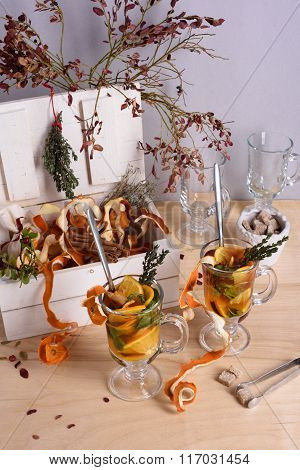 Winter warming drink: herbs,orange peel,cinnamon, thyme and box full of ingredients on wooden table.