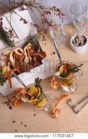 Hot mulled wine with orange slices, cinnamon, thyme on wooden table. Warming drink with ingredients.