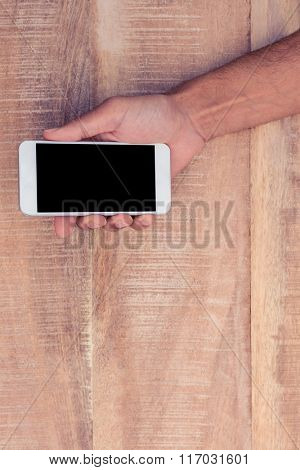 Directly above shot of man holding on phone over table